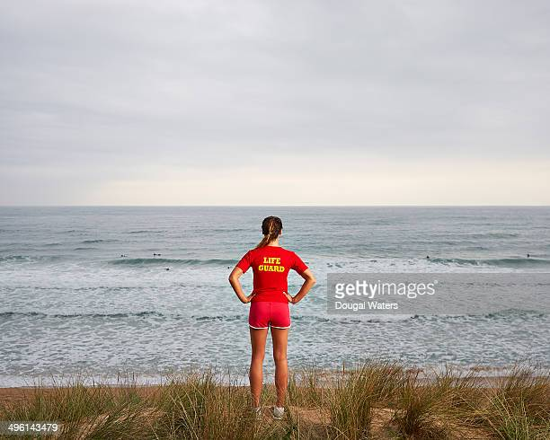 Female lifeguard watching surfers at sea.