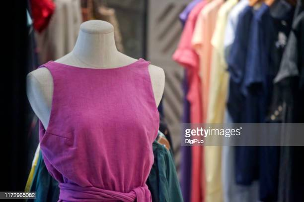 female like torso in pink casual dress against clothes hanging - roupa de mulher - fotografias e filmes do acervo