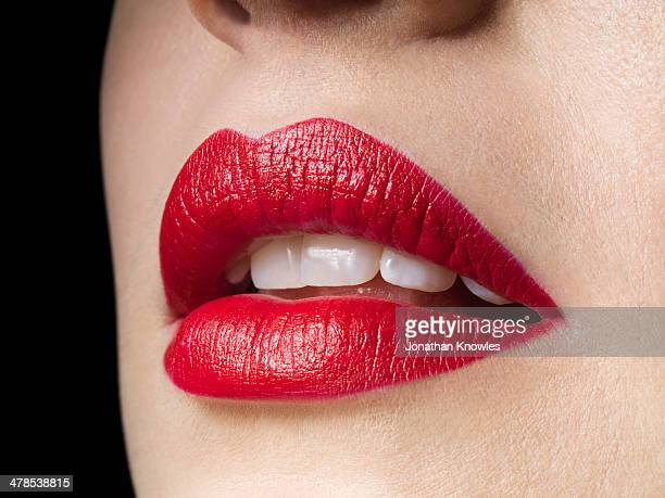 Female lips with red lipstick on, perfect teeth
