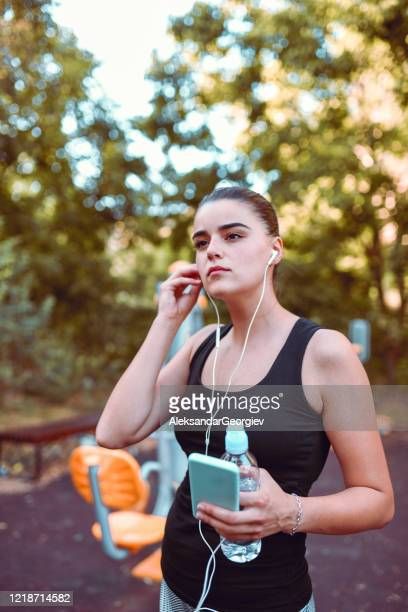female listening to music after outdoor training - colors soundtrack stock pictures, royalty-free photos & images