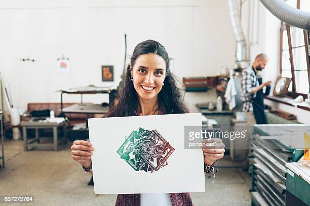 female lithography worker holding paper with new artifact - lithograph stock pictures, royalty-free photos & images