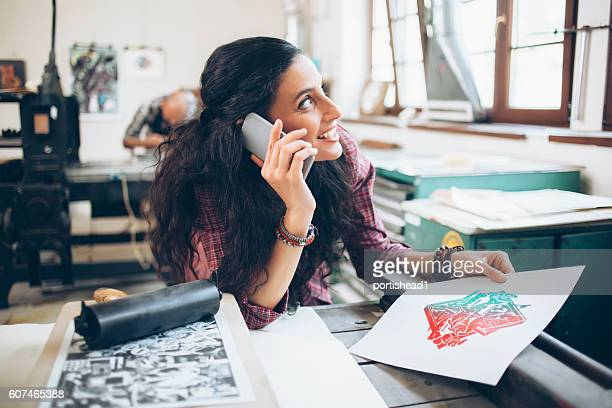 Female lithography worker using phone at printing house