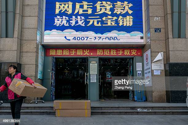 A female logistics worker is carrying the goods On the building's gate there are big advertisement about lending to Taobao shop owners An ecommerce...