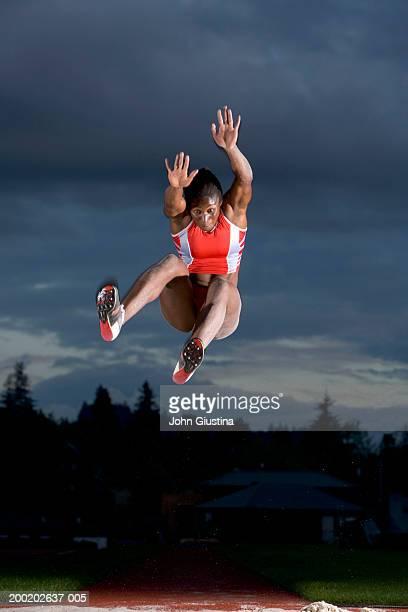 female long jumper in mid jump - 走り幅跳び ストックフォトと画像