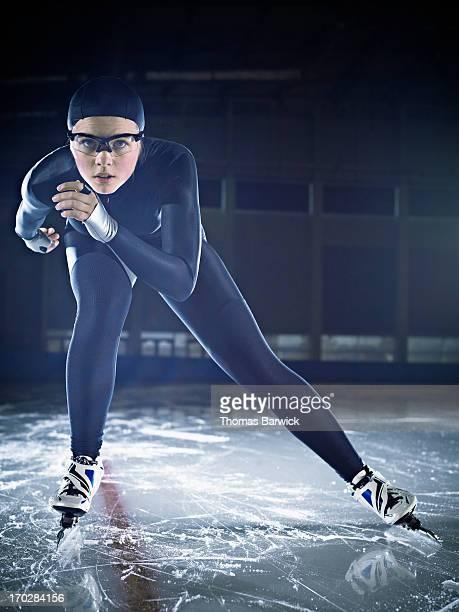 Female long track speed skater racing on track