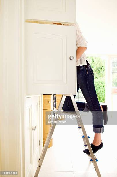 a female looking in a cupboard - step ladder stock photos and pictures