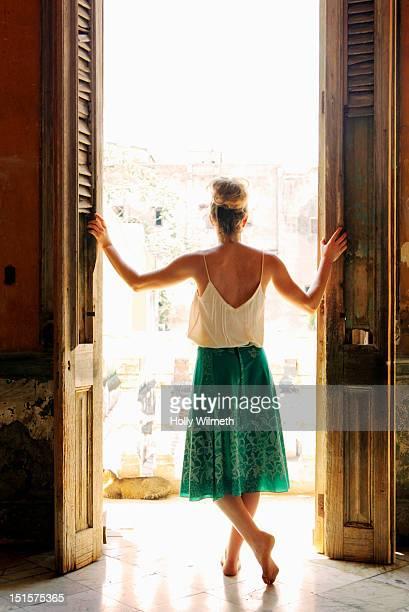 Female looking out veranda in Havana, Cuba.