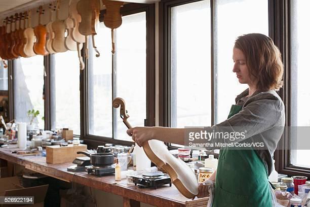 Female luthier in workshop