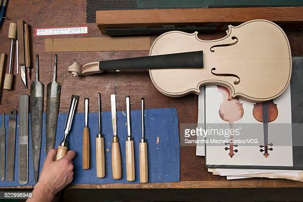Female luthier making violin