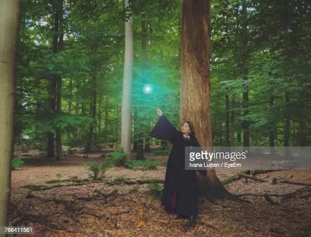 Female Magician Standing By Tree In Forest