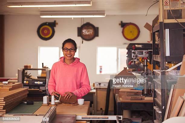female maker doing hand work in garage workshop. - タイ人 ストックフォトと画像