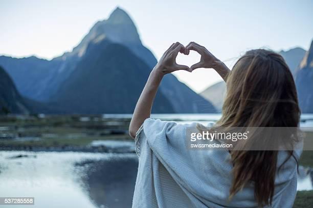 Female makes heart shape finger frame towards Milford Sound