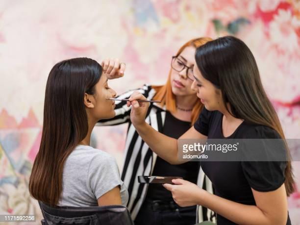 vrouwelijke make-up artiest en werknemer die make-up toepassen op klant - visagist stockfoto's en -beelden