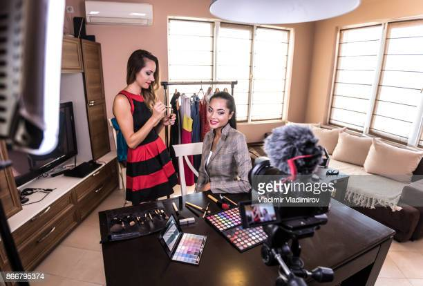Female makeup vloggers reviewing cosmetic products at home