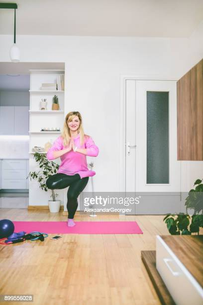 female making balance yoga meditation exercise in morning at home - aleksandar georgiev stock photos and pictures