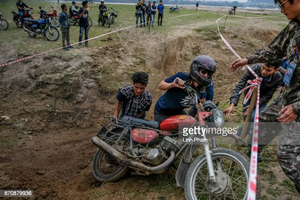 A female male Minsk motorcyclist crashes while trying to get over the dirt slope at an offroad race on November 5 2017 in Hanoi Vietnam A new...