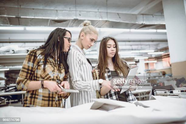 female manager analyzing new creation with coworkers - fashion collection stock pictures, royalty-free photos & images