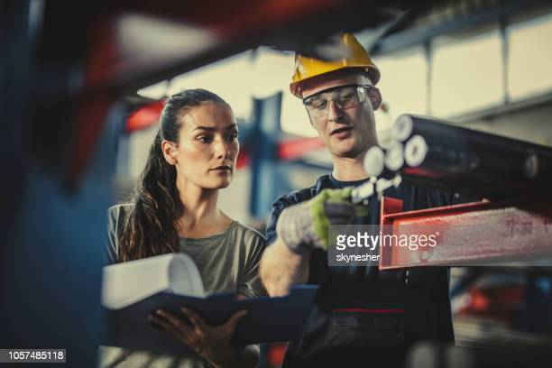 female manager and manual worker analyzing steel in industrial building. - metal industry stock pictures, royalty-free photos & images