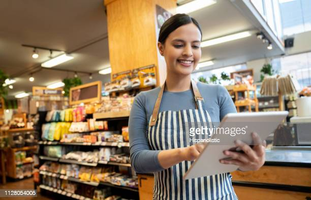 female manager at a supermarket holding tablet smiling - assistant stock pictures, royalty-free photos & images