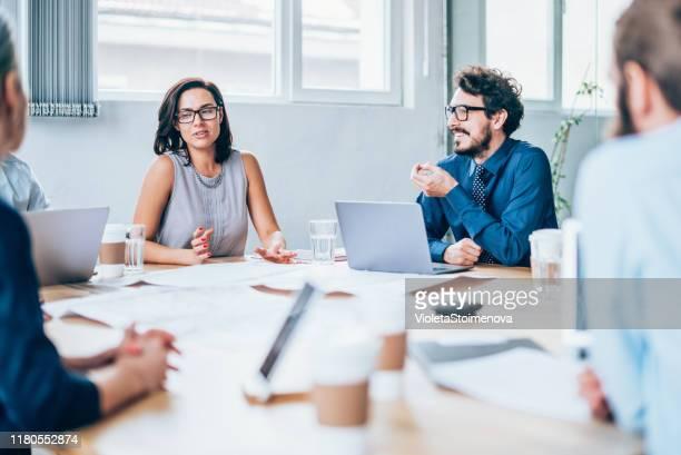 weibliche managerin diskutiert über wirtschaft - organisierte gruppe stock-fotos und bilder