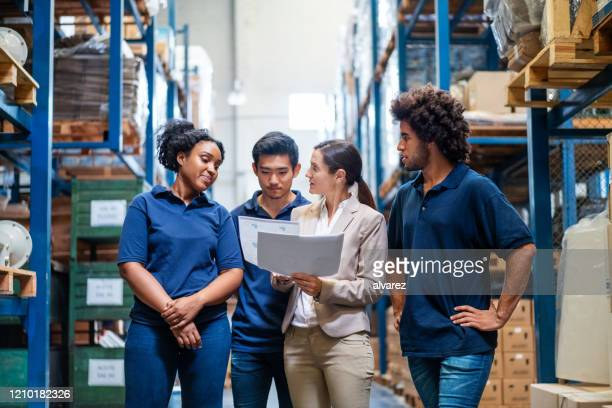 female manager discussing delivery schedules with staff - employee stock pictures, royalty-free photos & images