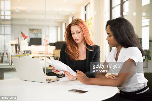 Female manager explaining documents to young businesswoman