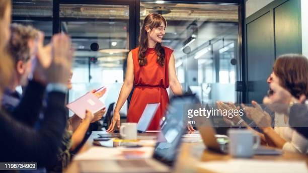 female manager getting an applause after a succesful meeting - red dress stock pictures, royalty-free photos & images