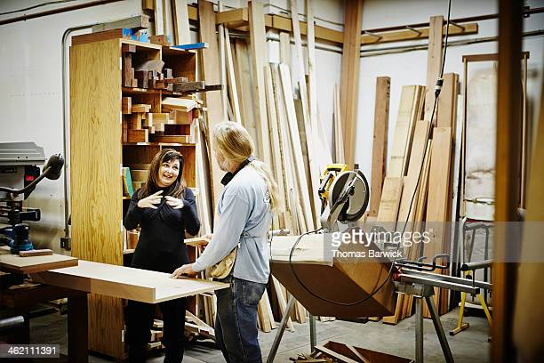 Female manager in discussion with male woodworker