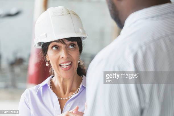 Female manager in hardhat talking to black worker