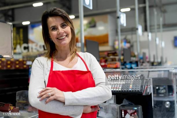 weibliche managerin eines supermarktes, die neben den kassen steht, lächelnd vor der kamera - weibliche person stock-fotos und bilder
