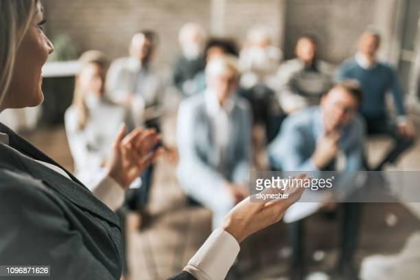 managerin im gespräch mit großen gruppe von kollegen auf ein seminar. - seminar stock-fotos und bilder