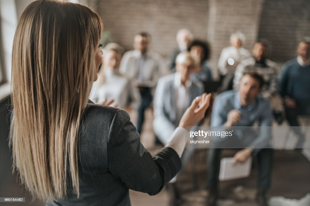 Female manager talking to large group of her colleagues on a business seminar. : Stock Photo