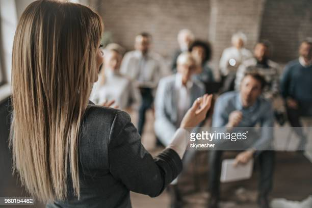 female manager talking to large group of her colleagues on a business seminar. - presentazione discorso foto e immagini stock