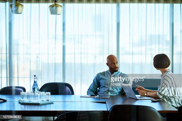 female manager talking to male colleague in board room - conflict stock pictures, royalty-free photos & images