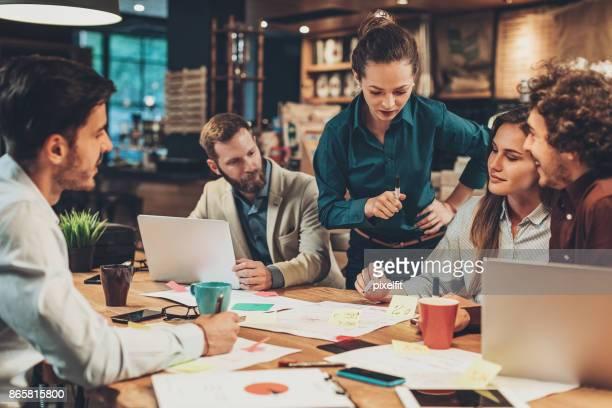gerente de mulher com sua equipe em uma reunião - autoridade - fotografias e filmes do acervo