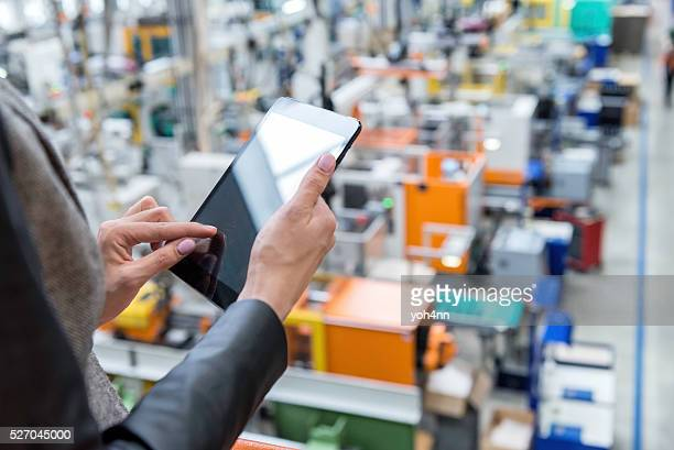 female manager working on tablet in factory - computer software stock pictures, royalty-free photos & images