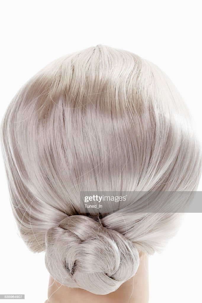 Female mannequin head wearing grey wig against white background : Stock Photo