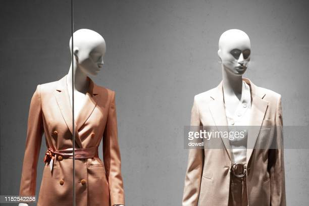 female mannequin wearing current clothing trends in a store window - mannequin stock pictures, royalty-free photos & images