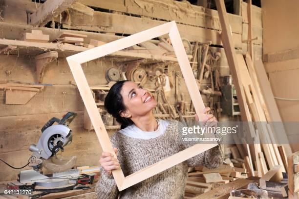 Female manual worker having fun in carpentry workshop
