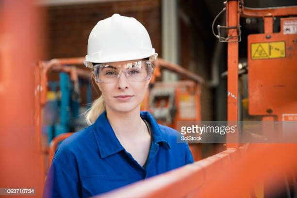 female manual worker - white jumpsuit stock pictures, royalty-free photos & images