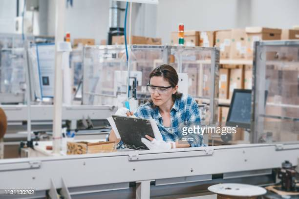 female manual worker taking notes at a factory - draft sports stock pictures, royalty-free photos & images