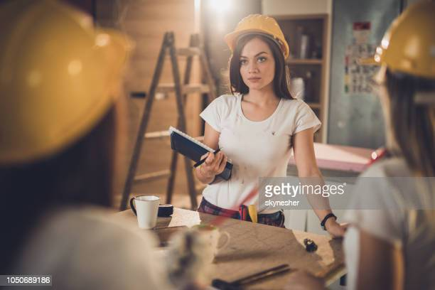 Female manual worker talking to her colleagues during home renovation process.
