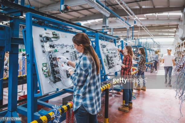 female manuel workers team working on the production line in factory - production line stock pictures, royalty-free photos & images