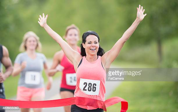 female marathon runner winning race - finish line stock pictures, royalty-free photos & images