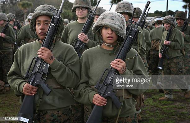 Female Marine recruits Princesse Aldrete and Genisis Ordonez stand in formation following handtohand combat training during boot camp February 27...