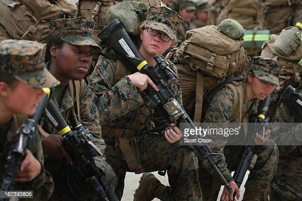 Female Marines rest following a 10 kilometer training hike carrying 55 pound packs during Marine Combat Training on February 22 2013 at Camp Lejeune...