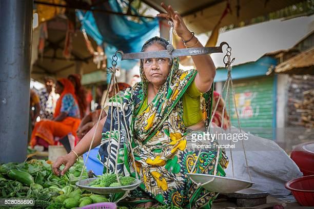 A female market trader weighs vegetables on a market on April 11 2016 in Khulna Bangladesh