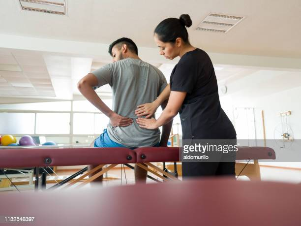 female massage therapist working on patient's back - sports medicine stock pictures, royalty-free photos & images
