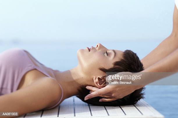 female masseuse giving young woman facial massage, side view - head massage stock photos and pictures