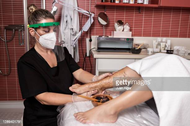 female masseuse smearing feet of client with mud - face mask beauty product stock pictures, royalty-free photos & images